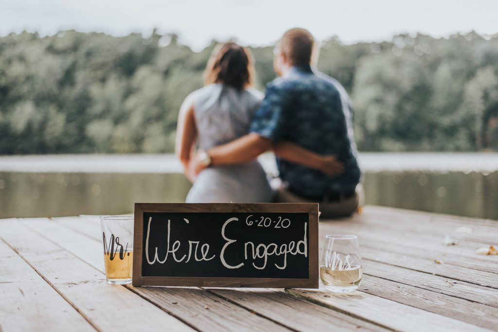 We're engaged sign with couple in background