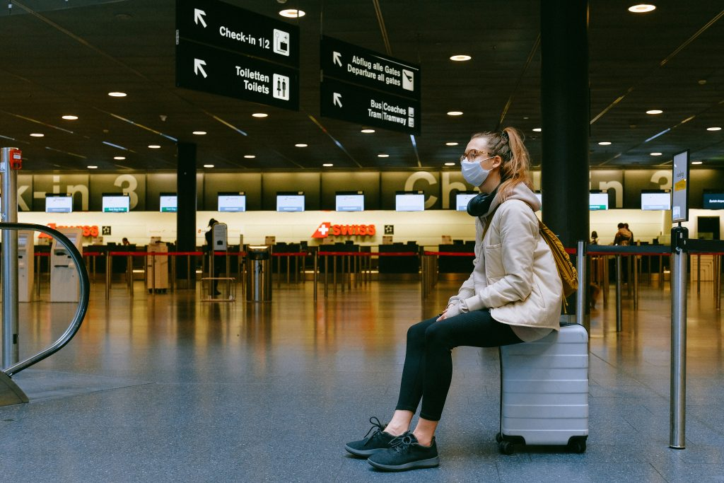 Wedding guest waiting in airport with mask