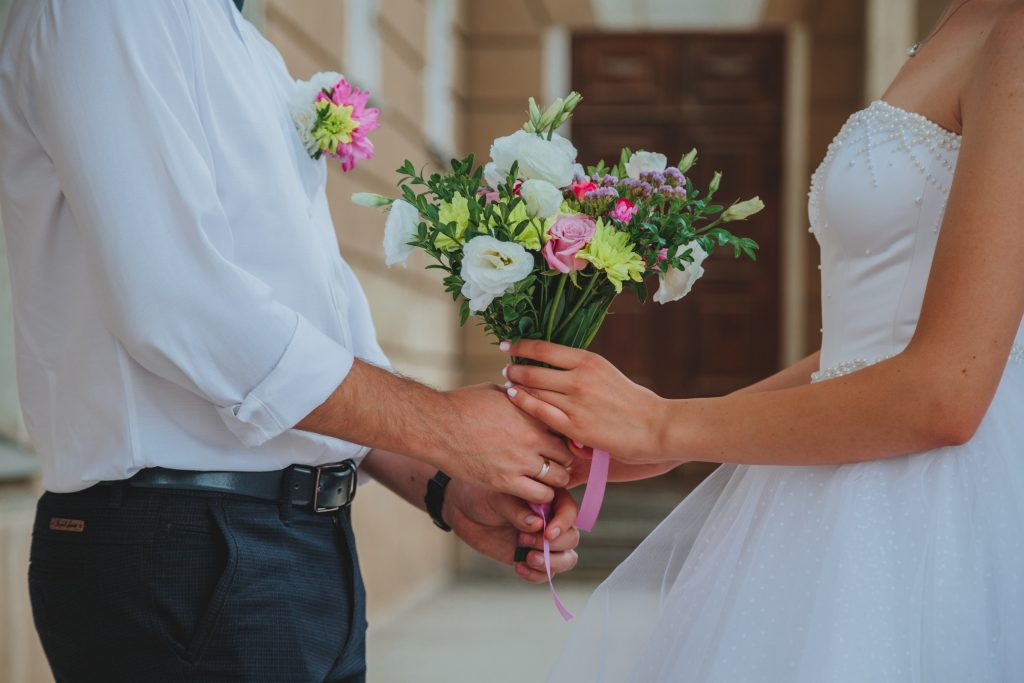 Couple holding wedding flowers together